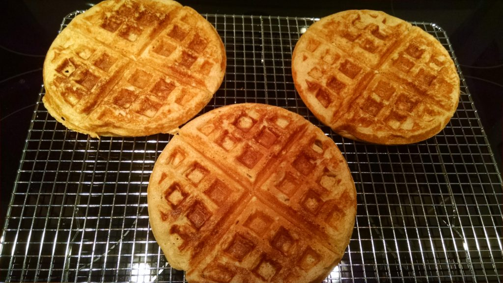 Waffles cooling on a stainless steel rack.